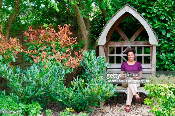 mixed race woman reading magazine in backyard - nature magazine stock pictures, royalty-free photos & images
