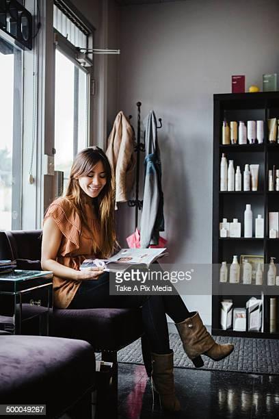 Mixed race woman reading magazine in salon