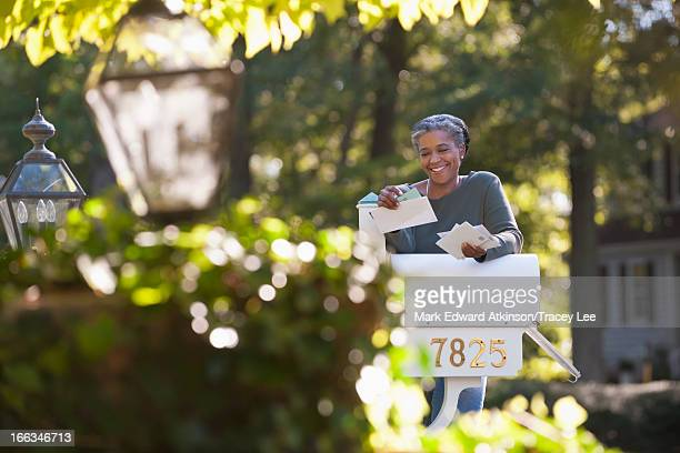 mixed race woman reading mail at mailbox - mailbox stock pictures, royalty-free photos & images