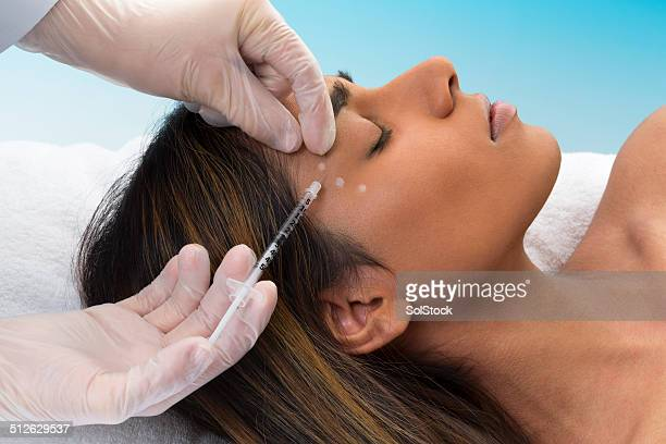 mixed race woman receiving botox injection - botox stock pictures, royalty-free photos & images