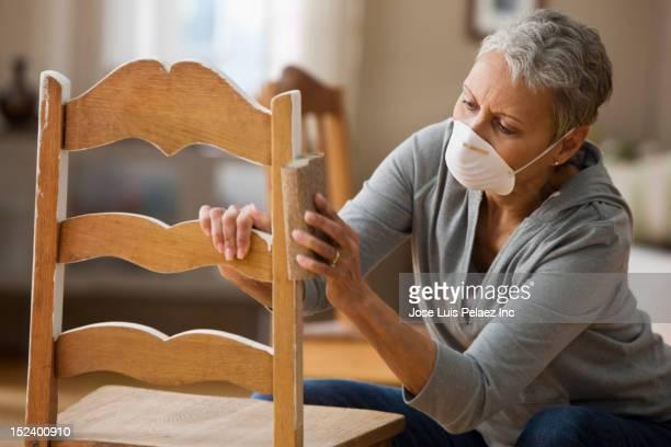 Mixed race woman refinishing chair