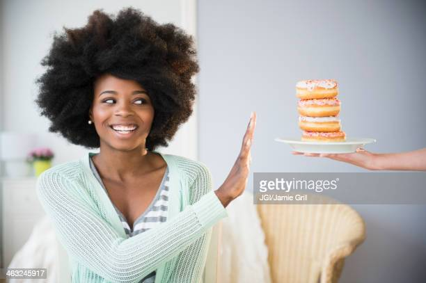 mixed race woman refusing donuts - refusing stock pictures, royalty-free photos & images