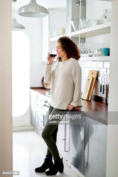 mixed race woman relaxing drinking red wine at home in kitchen - wine stock pictures, royalty-free photos & images