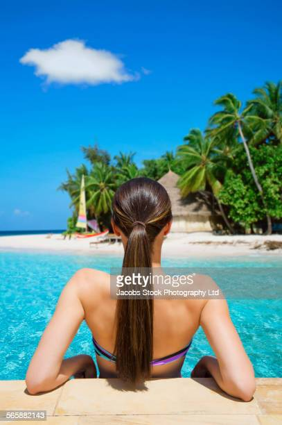 Mixed race woman relaxing in ocean on beach