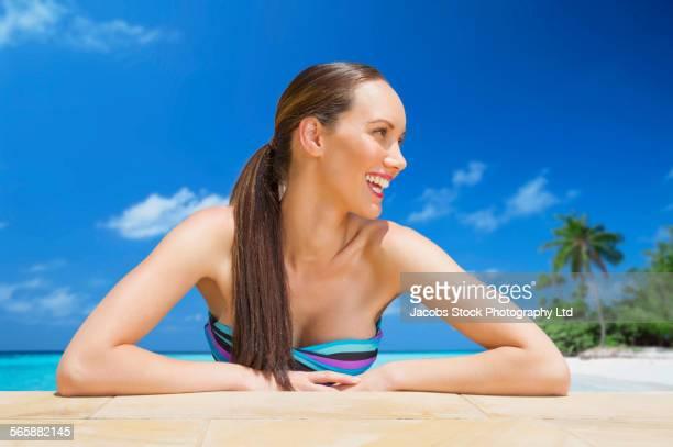 Mixed race woman relaxing in ocean on beach