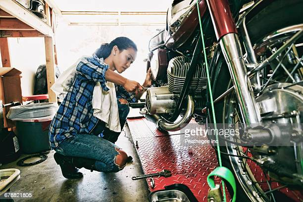 mixed race woman repairing motorcycle in garage - hobbies stock pictures, royalty-free photos & images