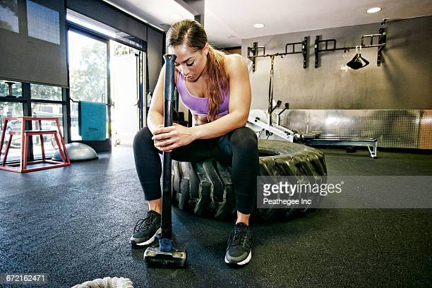 mixed race woman resting on tire holding sledgehammer in gymnasium - donna creola foto e immagini stock