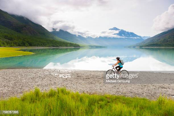 mixed race woman riding bicycle near lake - lakeshore stock pictures, royalty-free photos & images