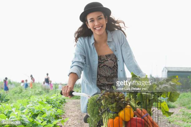 Mixed race woman riding bicycle with produce on farm