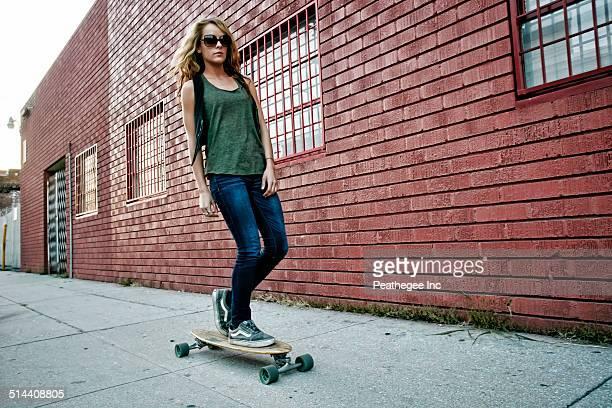 Mixed race woman riding skateboard on city street