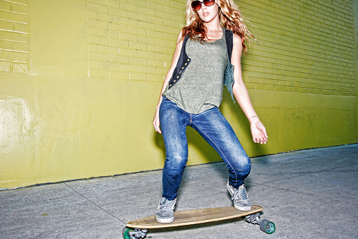 Mixed race woman riding skateboard on city street - gettyimageskorea