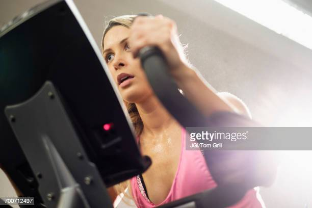 mixed race woman riding stationary bicycle - peloton stock pictures, royalty-free photos & images
