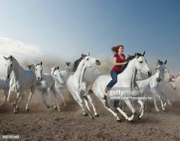 Mixed race woman riding wild horse in desert