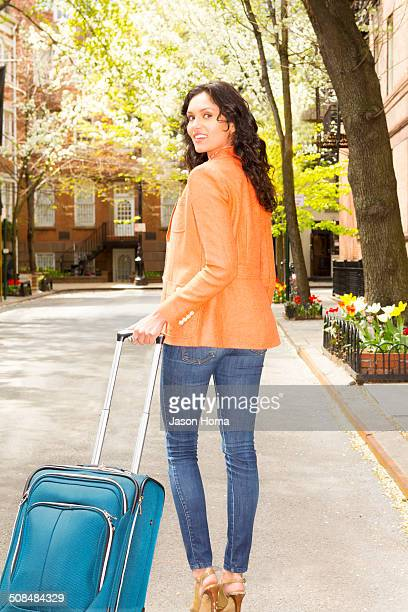 Mixed race woman rolling luggage on city street