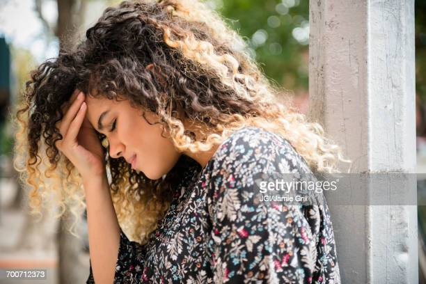 Mixed Race woman rubbing forehead