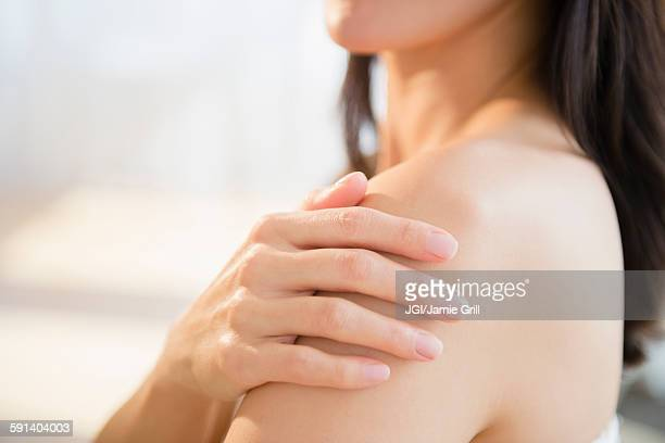 Mixed race woman rubbing lotion into skin