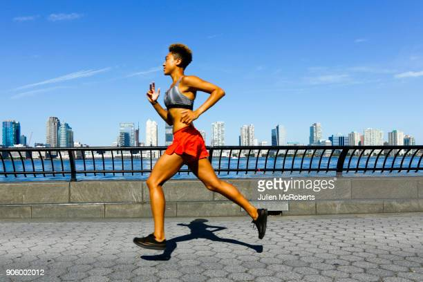 mixed race woman running at waterfront - joggeuse photos et images de collection