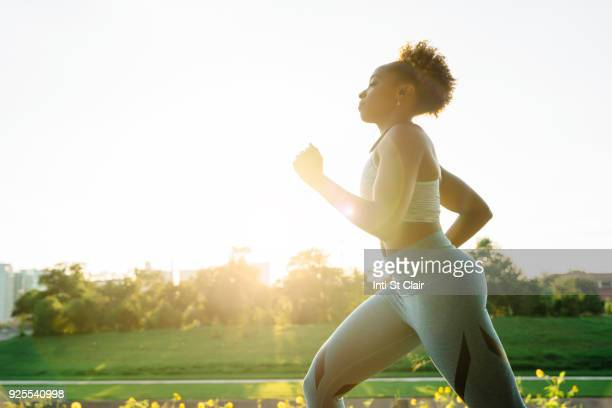 mixed race woman running in park - jogging stock photos and pictures