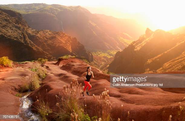 mixed race woman running in volcanic landscape near stream - active volcano stock pictures, royalty-free photos & images
