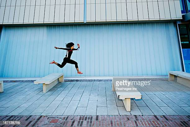 mixed race woman running on city street - hurdling track event stock pictures, royalty-free photos & images