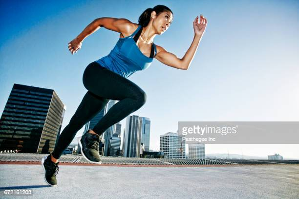 mixed race woman running on urban rooftop - sprinting stock pictures, royalty-free photos & images
