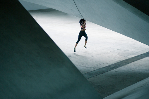 Mixed Race woman running under urban structure - gettyimageskorea