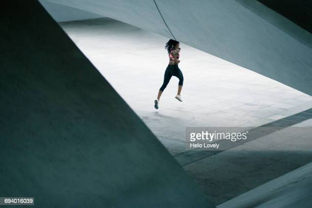 Mixed Race woman running under urban structure