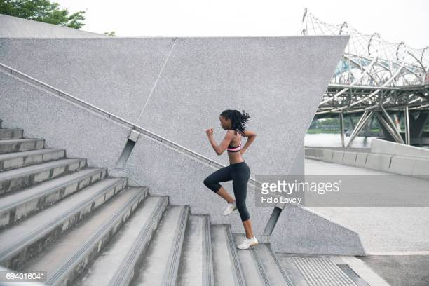 Mixed Race woman running up urban staircase