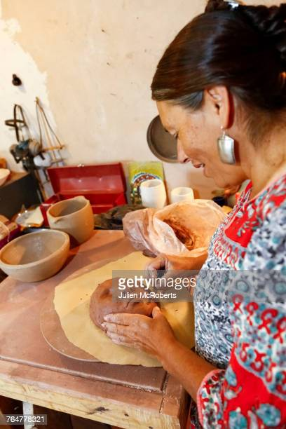 Mixed race woman shaping clay mask in art studio