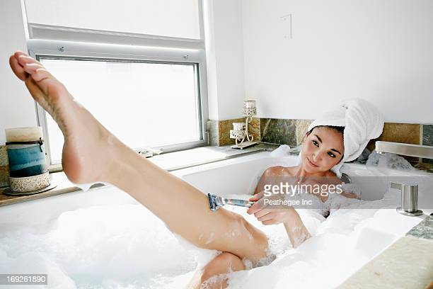 Mixed race woman shaving in bubble bath