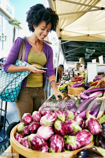 Mixed race woman shopping at vegetable stand