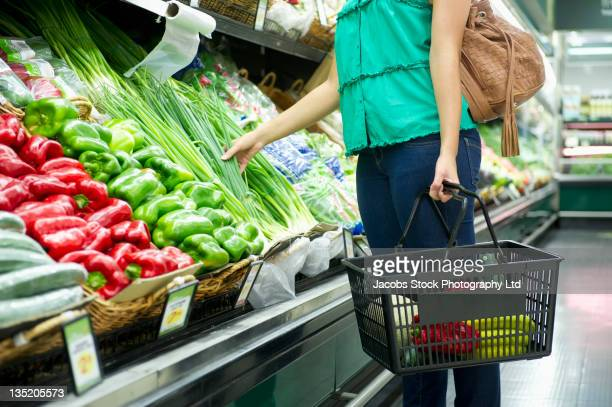 mixed race woman shopping for vegetables - basket stock photos and pictures