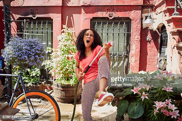 Mixed Race woman singing and playing air guitar in garden