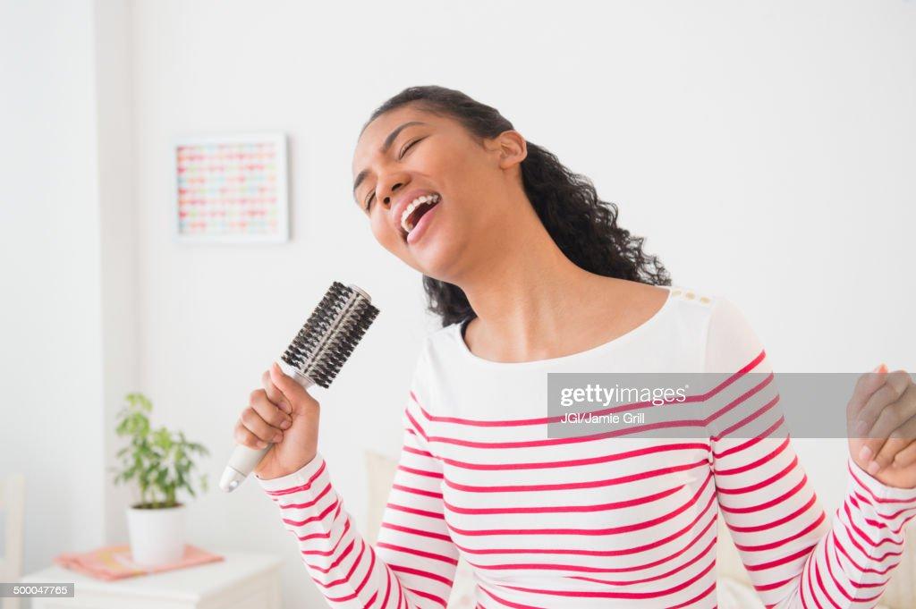 Mixed race woman singing into hairbrush : Stock Photo