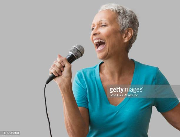 Mixed race woman singing with microphone