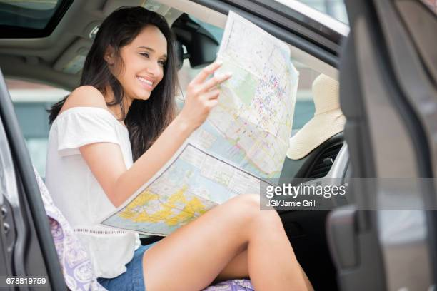 Mixed Race woman sitting in car reading map