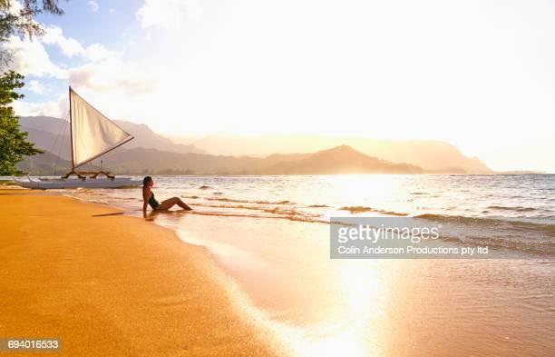Mixed Race woman sitting on beach near sailboat