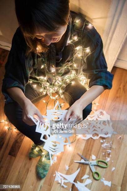 Mixed Race woman sitting on floor wrapped in string lights holding snowflake