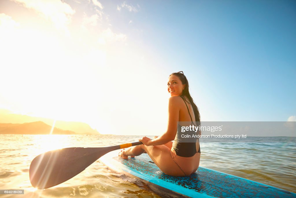 Mixed Race woman sitting on paddleboard in ocean : Stock Photo