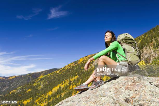 Mixed race woman sitting on rock