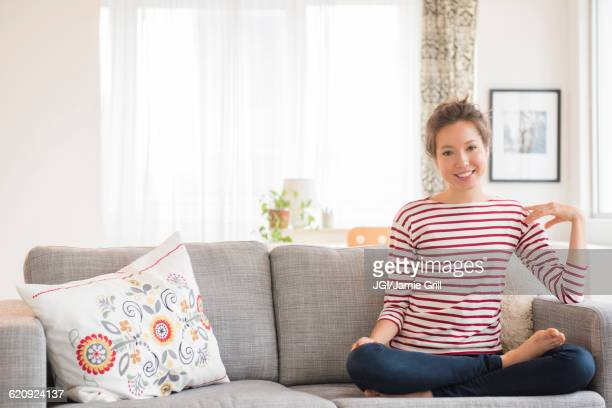 Mixed race woman sitting on sofa