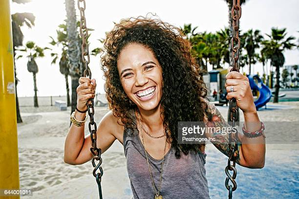 Mixed race woman sitting on swing at beach