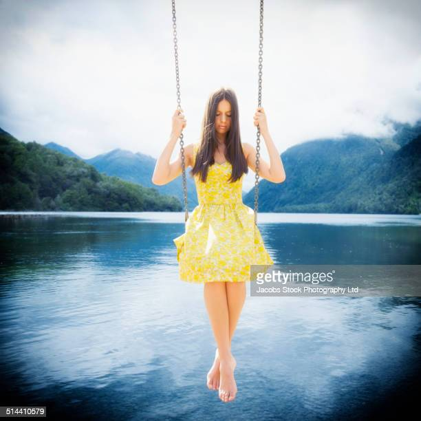 Mixed race woman sitting on swing over still lake