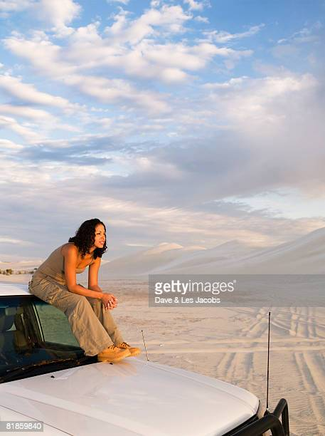 Mixed Race woman sitting on top of truck