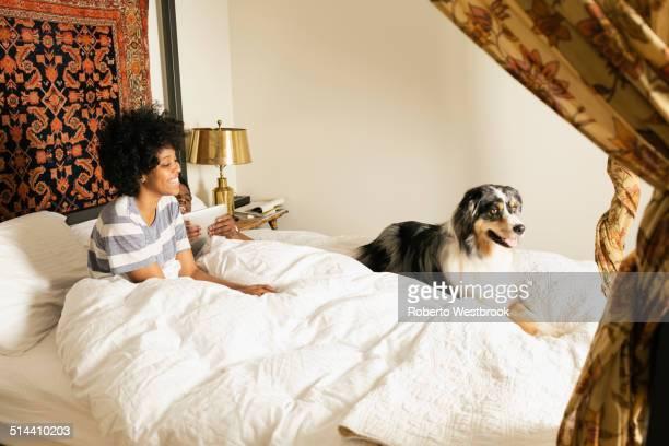 mixed race woman sitting with dog in bed - roberto ricciuti foto e immagini stock