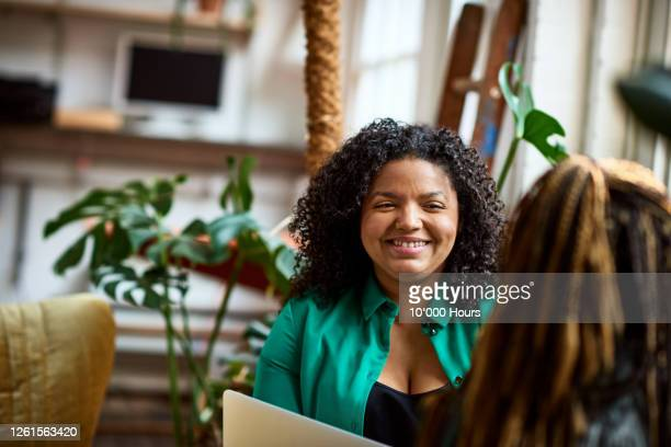 mixed race woman smiling at colleague in office meeting - discussion stock pictures, royalty-free photos & images