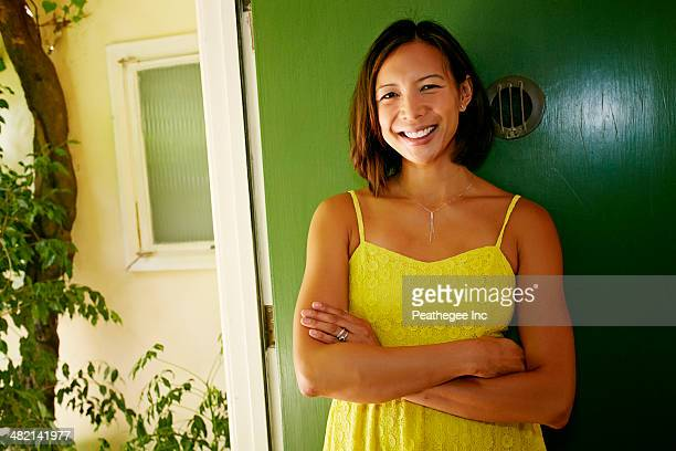 Mixed race woman smiling at front door