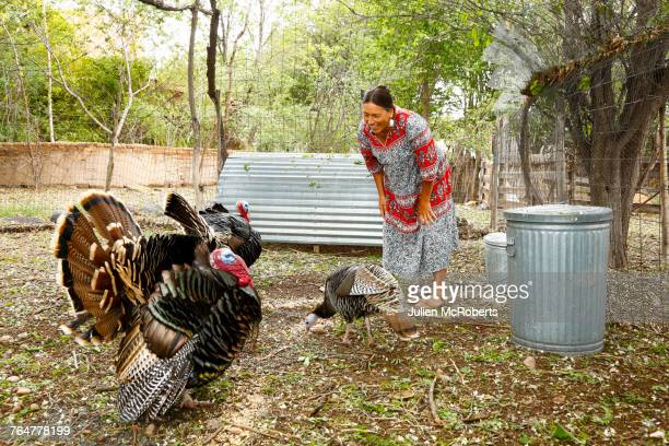 Mixed race woman smiling at turkeys