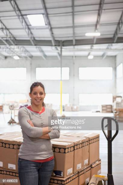 Mixed race woman smiling by pallet of boxes in warehouse