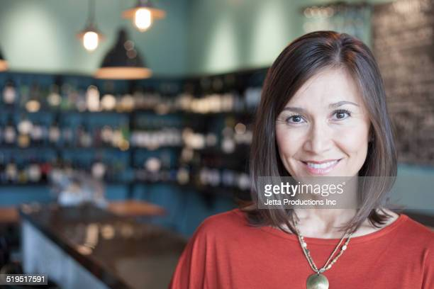 Mixed race woman smiling in wine bar